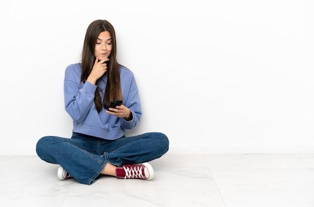 Молодая женщина сидит на полу, думает и отправляет сообщение