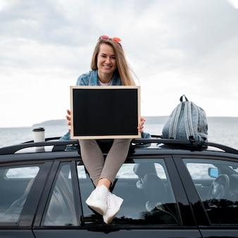 Giovane donna seduta in cima alla macchina