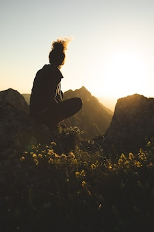 Young woman sitting on top of the mountain and enjoying the view during sunset