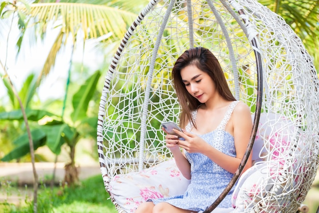 Young woman sitting use smartphone in white swing