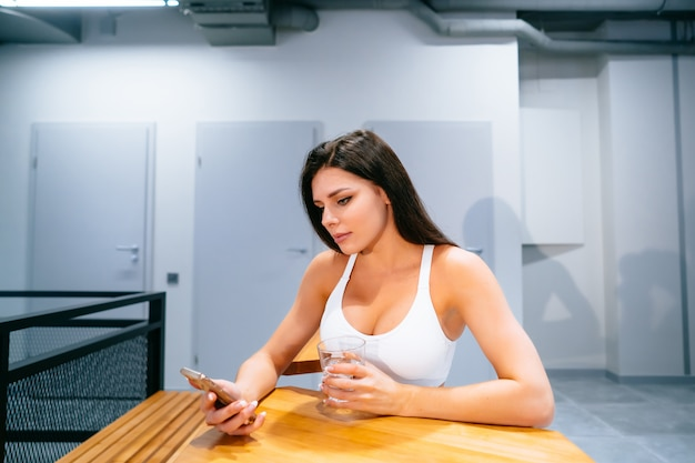 Young woman sitting and using smartphone after training