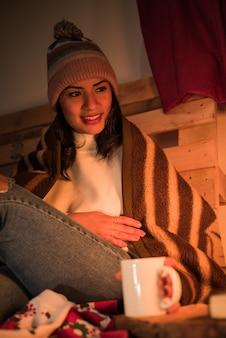 겨울 담요에 싸여 난로 빛을보고 겨울 모자와 흰색 스웨터를 입고 앉아 젊은 여자