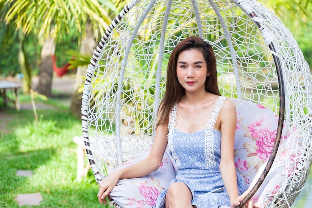 Young woman sitting in white swing