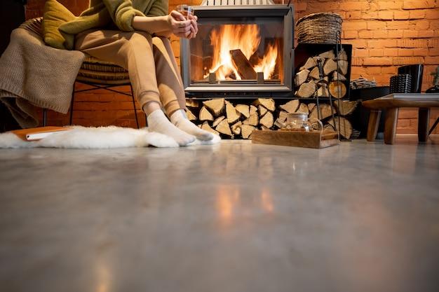 Молодая женщина, сидящая с напитком у горящего камина, обрезанное изображение без лица. уютный интерьер в стиле лофт