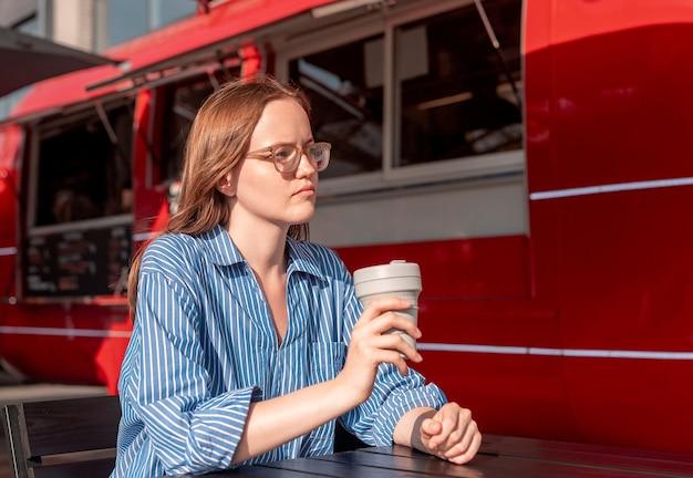Молодая женщина, сидящая со складной эко-кофейной чашкой возле фургона с едой на красной улице в солнечный летний день ...