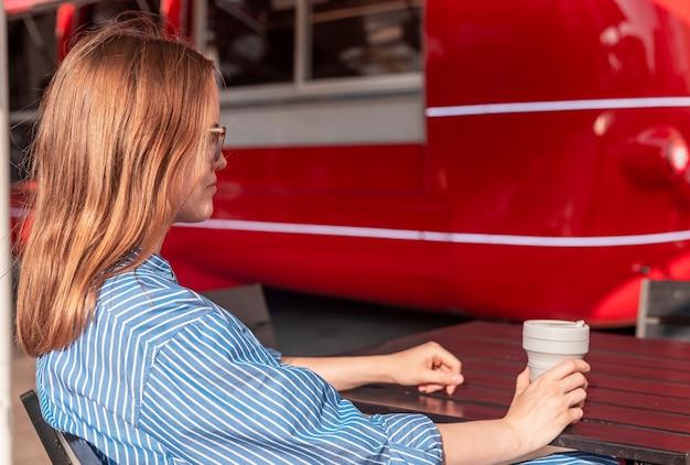 Молодая женщина, сидящая со складной эко-кофейной чашкой возле грузовика с едой на красной улице в солнечный летний день