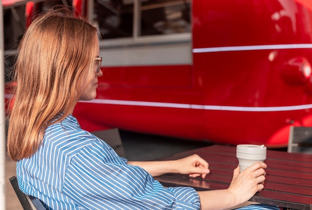 Young woman sitting with collapsible eco coffee cup near red street food truck at sunny summer day
