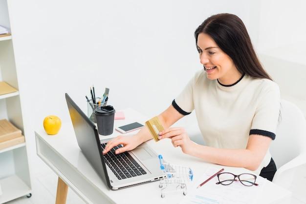 노트북 테이블에 신용 카드로 앉아 젊은 여자