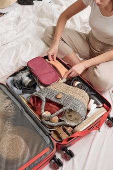 ベッドに足を組んで座って、休暇旅行のために荷物を詰める若い女性