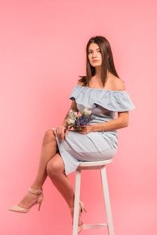花の花束と椅子に座っていた若い女性
