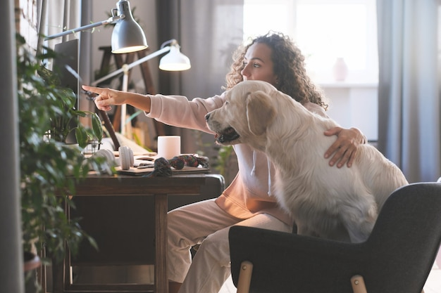 コンピューターの前で犬と一緒に座って、コンピューターを指差して何かを見せている若い女性