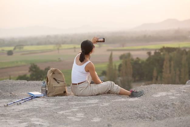 휴대 전화와 함께 앉아 젊은 여자. 일몰에 높은 산 관광 경로입니다.