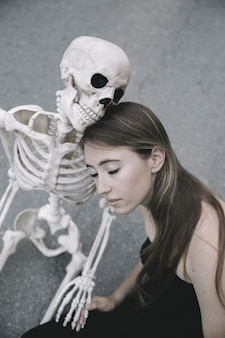 Young woman sitting with skeleton and holding its hand