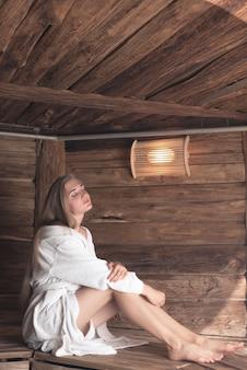 Giovane donna che si siede sul banco di legno che dorme nella sauna