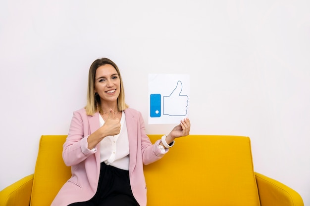 Young woman sitting on yellow sofa holding like icon showing thumbup sign