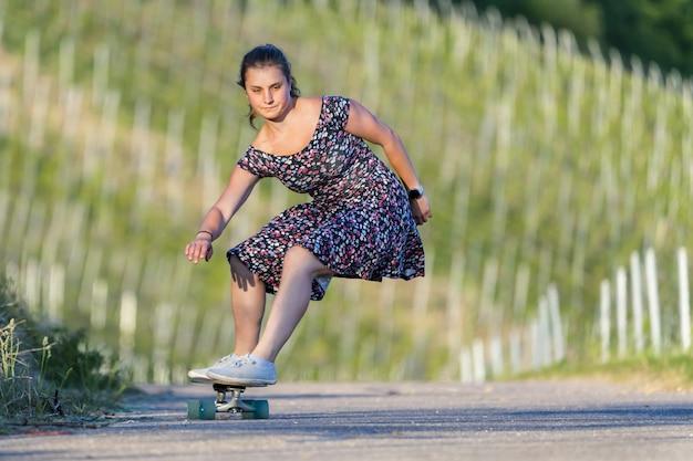 緑に囲まれた空の道でスケートボーディングの若い女性