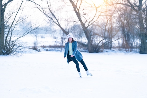 凍った池でスケートをする若い女性