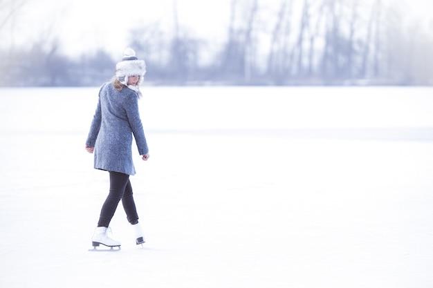 얼어 붙은 연못에서 스케이트를 타는 젊은 여자