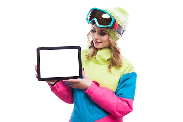 Young woman in ski suit hold blank tablet