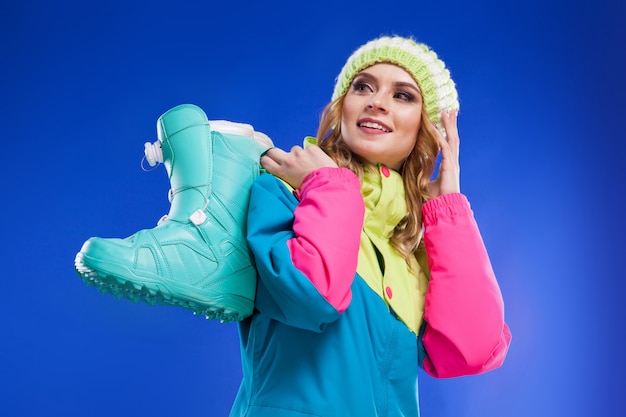 Young woman in ski suit hold blue ski boots