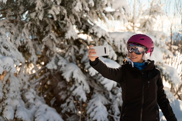 A young woman in skiing clothes, a pair of ski goggles and a ski helmet making a selfie in a ski resort next to a snowy tree