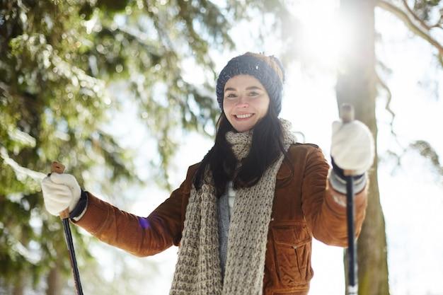 日光の下でスキーの若い女性