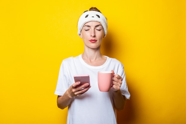 Young woman in a sleep harness, with closed eyes holds a phone and with a cup of coffee on a yellow background.