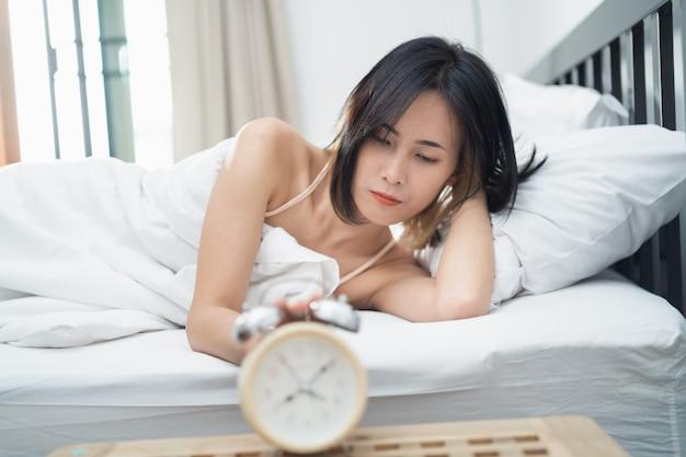 집에서 침실에서 자고있는 젊은 여자와 알람 시계