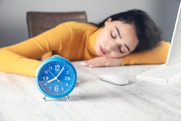 Молодая женщина спит на рабочем месте.