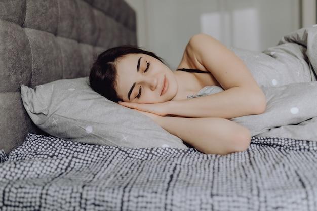 眠っている若い女性。ベッドで寝ている若い笑顔美人