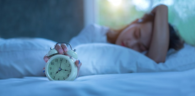 Young woman sleeping in bed with alarm at night