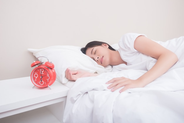 目覚まし時計の横にベッドで寝る若い女性