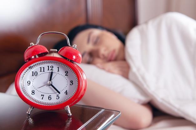 알람 시계 앞 침대에서 자 고하는 젊은 여자. 수면 시간