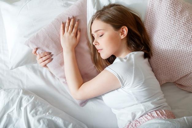 ベッドで寝ている若い女性。ブロンドの十代の少女の肖像画は、白いピンクの枕で健康的な睡眠をとっています。パジャマ姿のティーンエイジャーの女の子は、朝の時間に寝室で寝ています。上面図。
