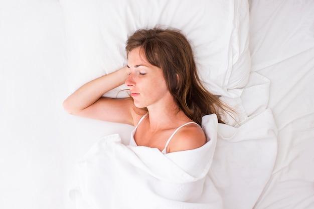 Молодая женщина спит в постели. понятие о хорошем сне, мечтах, снотворных. плоская планировка, вид сверху