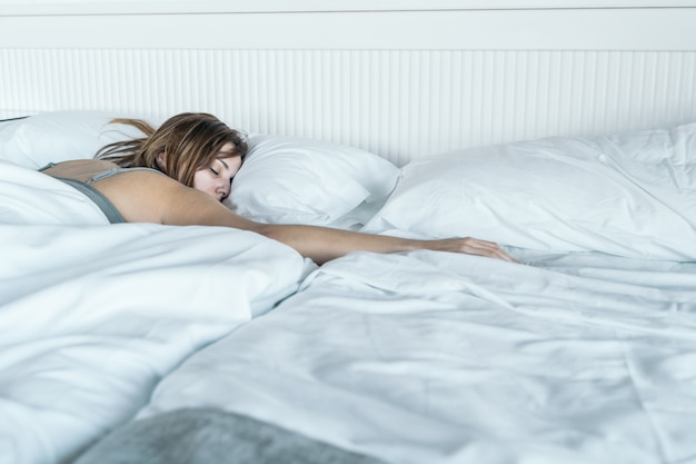 彼女の胃の彼女のベッドで寝ている若い女性。