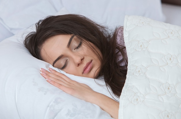自宅のベッドで白いリネンの寝間着で寝ている若い女性