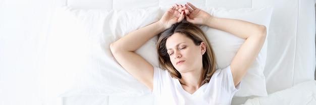 白いベッドで寝ている若い女性トップビュー柔らかく快適な寝具のコンセプト