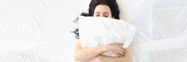 Молодая женщина спит в белой кровати с подушкой на лице, вид сверху, удобное и мягкое постельное белье