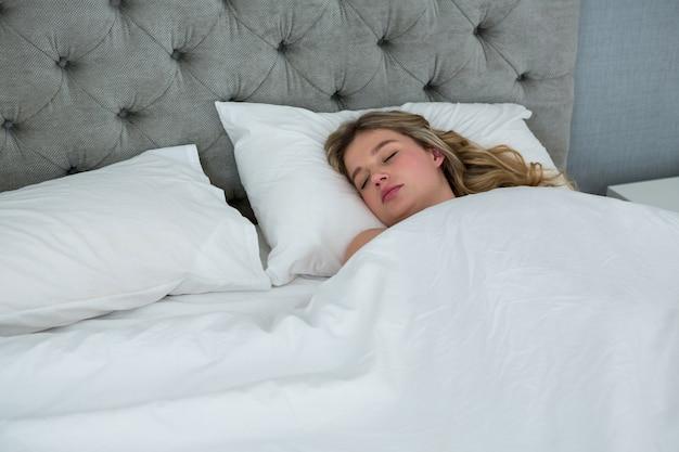 Молодая женщина спит на своей кровати