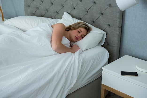 彼女のベッドで寝ている若い女性