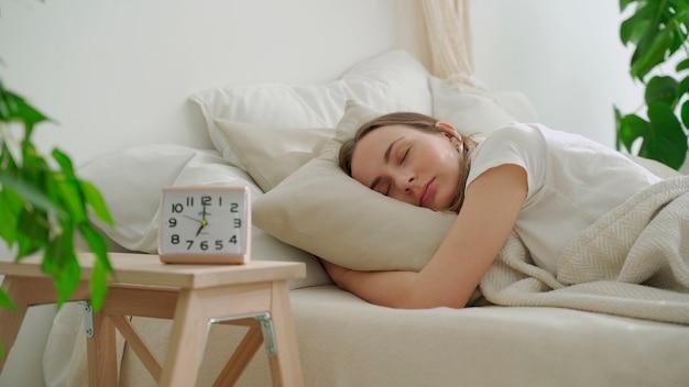Молодая женщина спит на белой подушке в постели женщина мирно спит в постели