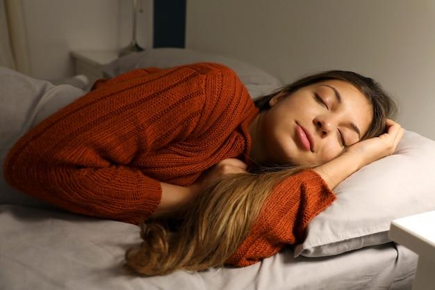 Молодая женщина мирно спит на кровати