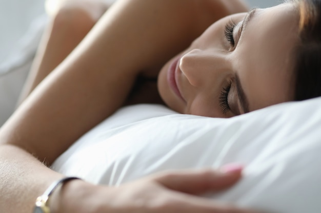 白い寝具で安らかに寝ている若い女性