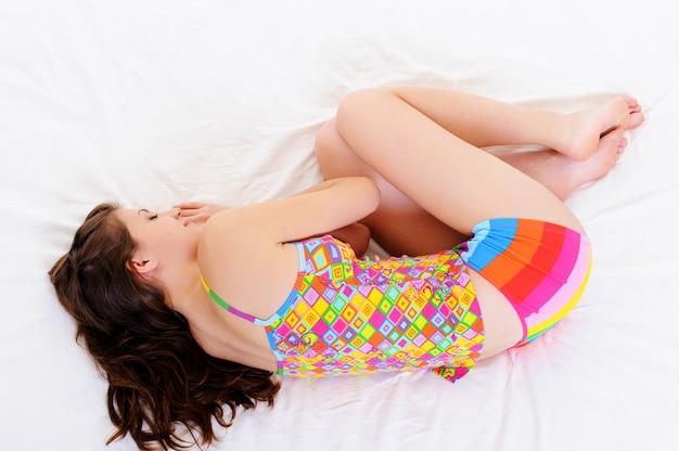 ベッドで寄り添って寝ている若い女性