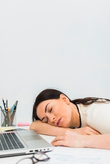 Young woman sleeping at table with laptop