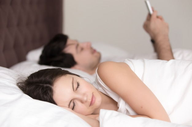 Young woman sleeping while her boyfriend using smartphone in bed