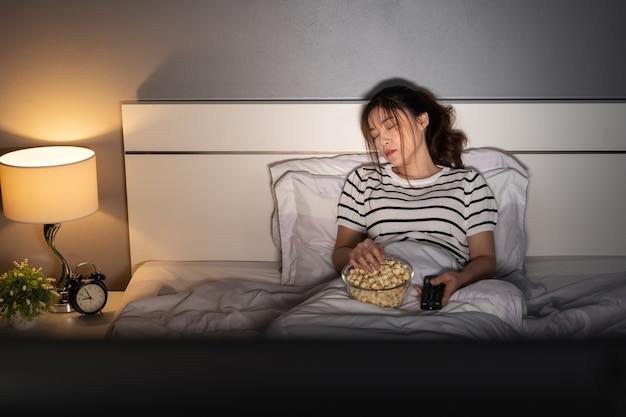 Молодая женщина спит во время просмотра телевизора на кровати ночью