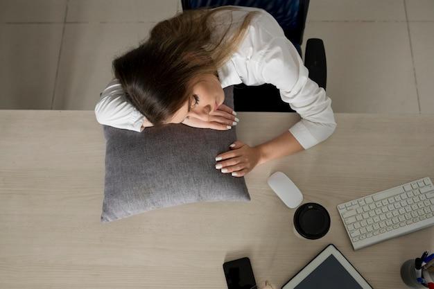 Giovane donna che dorme al lavoro