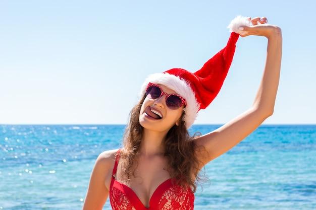 熱帯のビーチでリラックスしたサンタ帽子でスリムな若い女性
